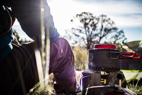 Backpacker sits next to Primus stove