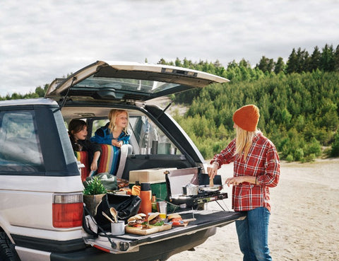 A family cooks at their outdoor cooking station in the back of their vehicle.