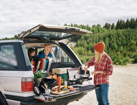 Camping family prepares a meal on a Primus stove