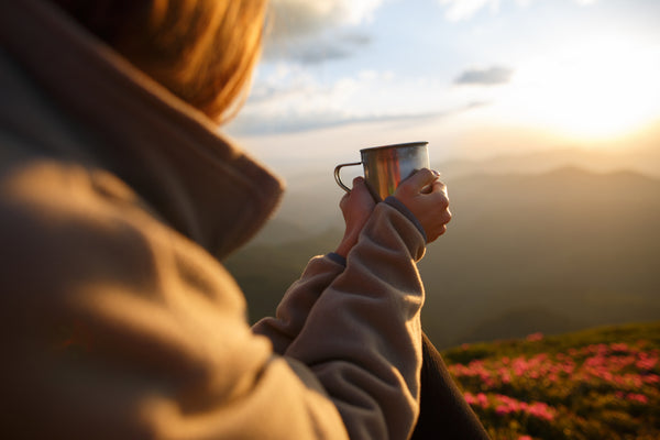 Women holds mug in both hands sitting at a viewpoint while the sun rises.