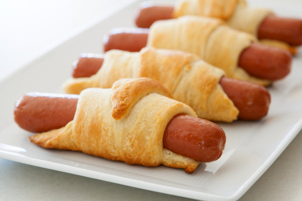 Four vegan hot dogs wrapped in crescent rolls lined up on a white rectangle plate.