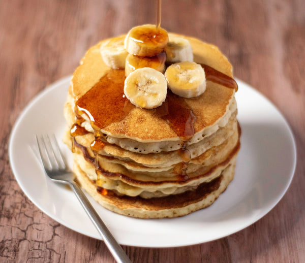 A stack of six pancakes topped with bananas and drizzled with maple syrup sit on a white plate with a fork.