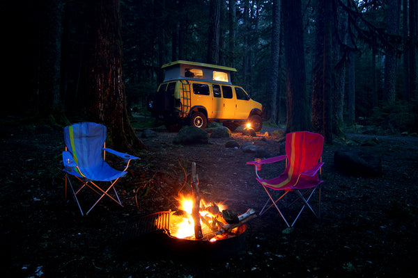 Off road yellow van in woods with camp chairs and a campfire.