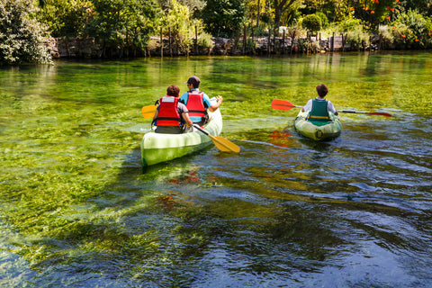 A family experiences adventure travel in the form of kayaking on a pristine forest lake.