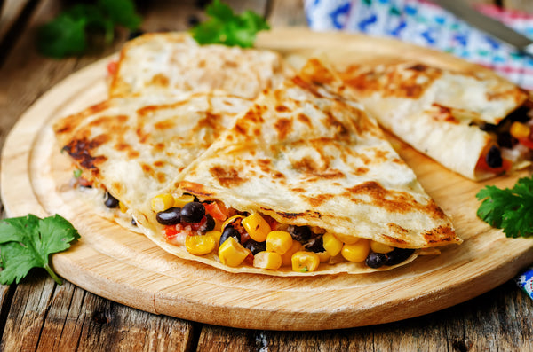 Grilled quesadillas with corn and black beans on a wooden plate surrounded by herbs.