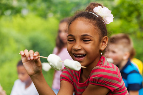 A young girl holds marshmallows on a stick close to her mouth, ready to eat.