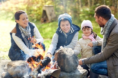 A family laughs while enjoying a campfire.