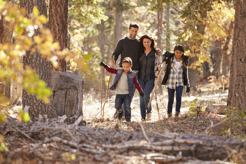 A family hikes through the woods