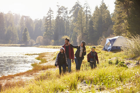 A family on a camping trip surveys the surrounding lake area.