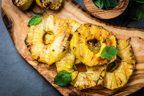 Grilled pineapple on a wooden plank.