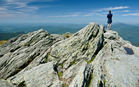 A hiker stands atop a vista on the Vermont Long Trail.