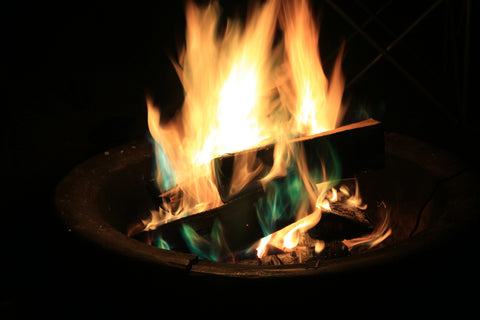A campfire shines with green colorant in it.