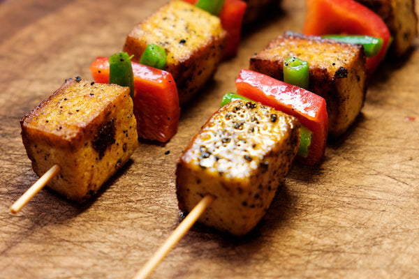 Season tofu, red peppers, and herbs on wooden skewers.