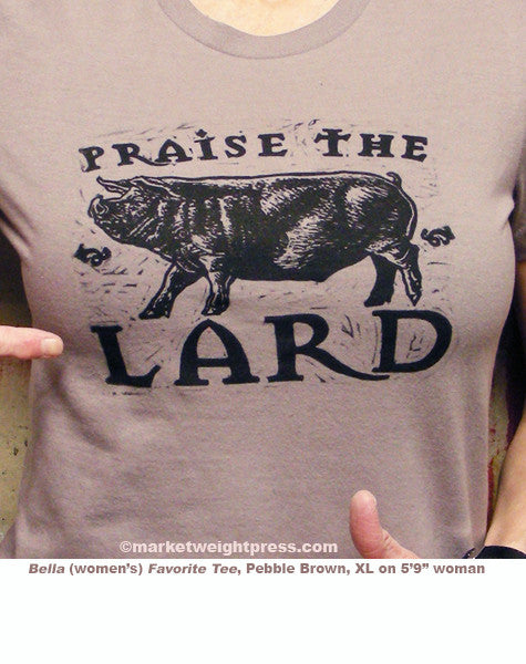 block-printed Praise the Lard design on light brown tee. Woman points to word 'Lard' with thumbs up