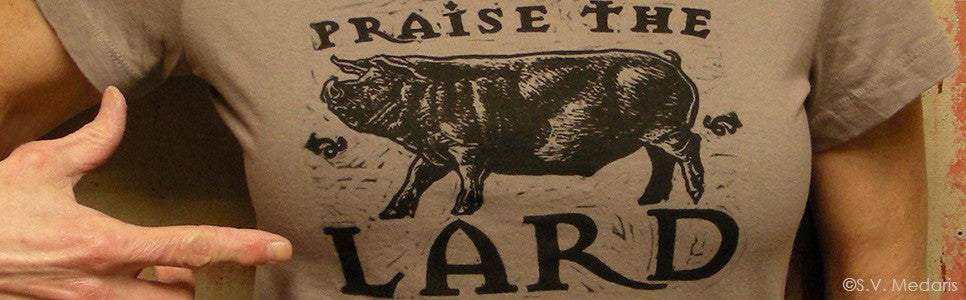 Praise the Lard design on chest of light brown shirt