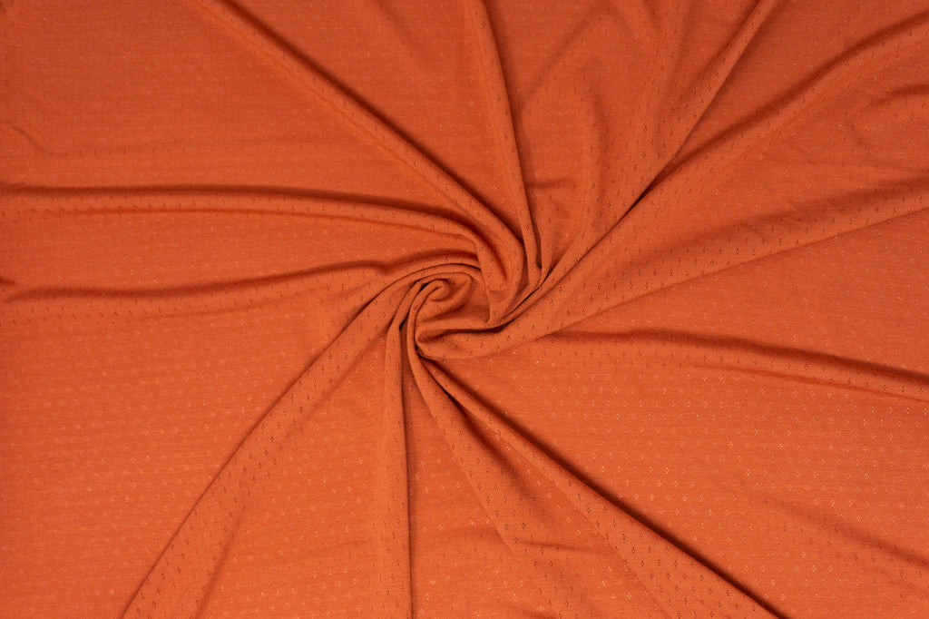Burnt Orange knit fabric with small lace like holes