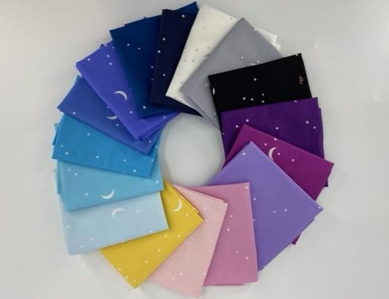 Rainbow of quilting cotton that is blue, pink, purple, and grey with moons and stars
