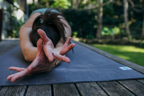Girl doing yoga in child's pose with hands facing up on Mukti Flow Mat