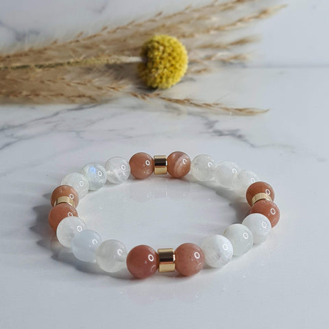 Samayla Jewellery's Moonstone and Sunstone celestial energy bracelet. Made with semi-precious gemstones, the bracelet is a milky white and pink colour with gold accents.