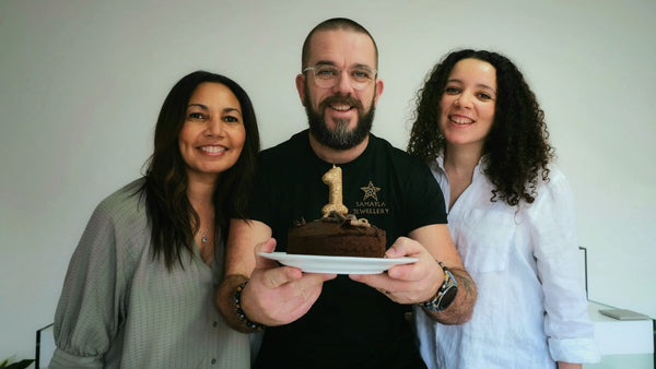 A photo of the Samayla team holding a birthday cake with a '1' candle.