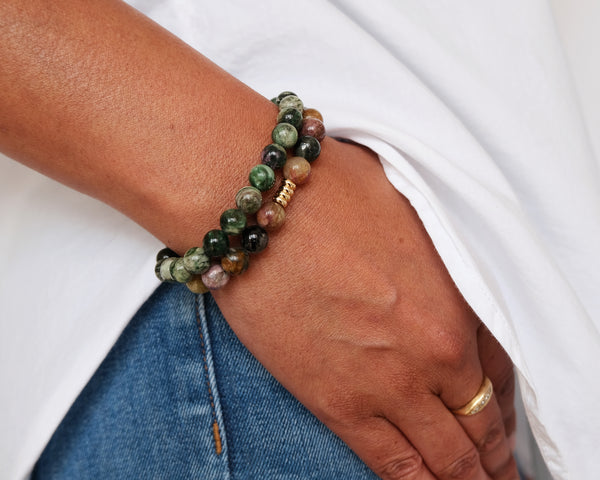 Green Lepidolite and Rainbow Tourmaline semi-precious gemstone beaded bracelets. They're worn on a wrist with the hand tucked into a denim jean pocket, contrasted with a crisp white shirt.