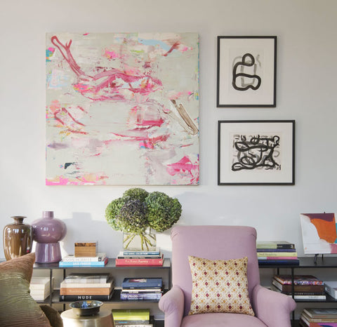 Wall of a living room, with a large abstract piece of art hanging on the wall, complemented by two smaller pieces. A bookshelf against the wall obscured by a light purple arm chair