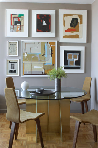 Dining room with table, chairs, and a back wall filled with art