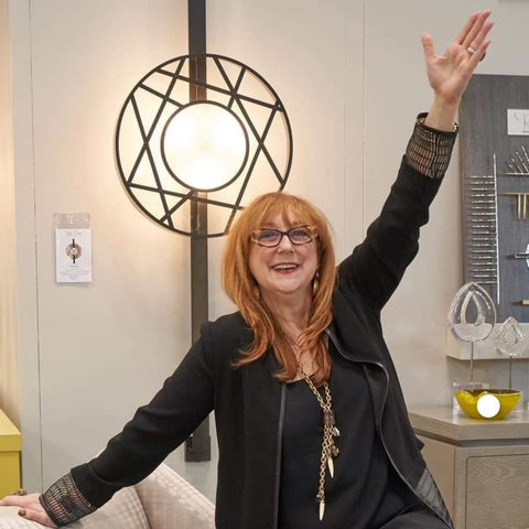 Robin Baron posing in front of one of her lighting designs