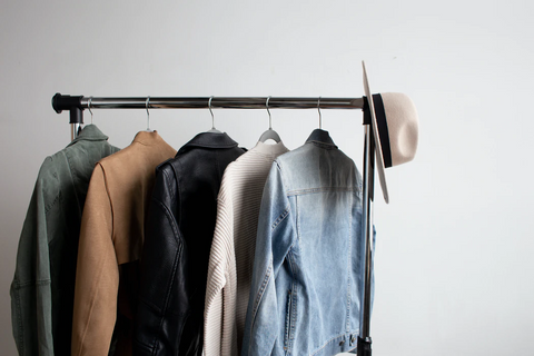 A clothes rack stands against a wall, with 5 different jackets hanging on it and a hat dangling off the right side