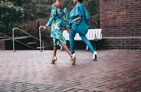 Two women walk on a brick path in brightly colored outfits, chic and stylish. Both are blue and green dominant
