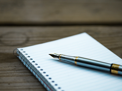 A fountain pen rests on a notebook on a wooden table