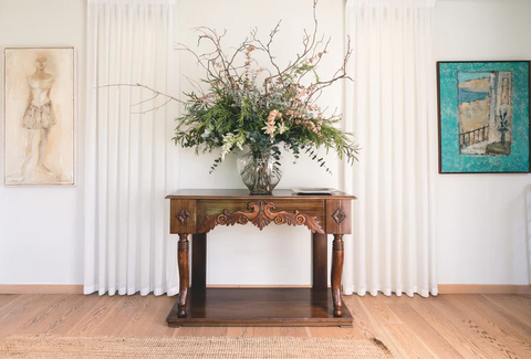 Decorative wooden table with a vase and many flowers on it. Framed on either side by curtains and pieces of art