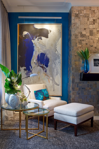 Corner of living room with nested side tables, an armchair with ottoman, and a large abstract blue painting on a blue wall