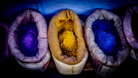 3 sacks with brightly colored powder that is used to dye fabric. Purple, yellow, and blue.
