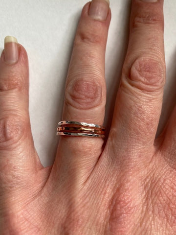 3 Silver and Copper stacking rings worn on a finger