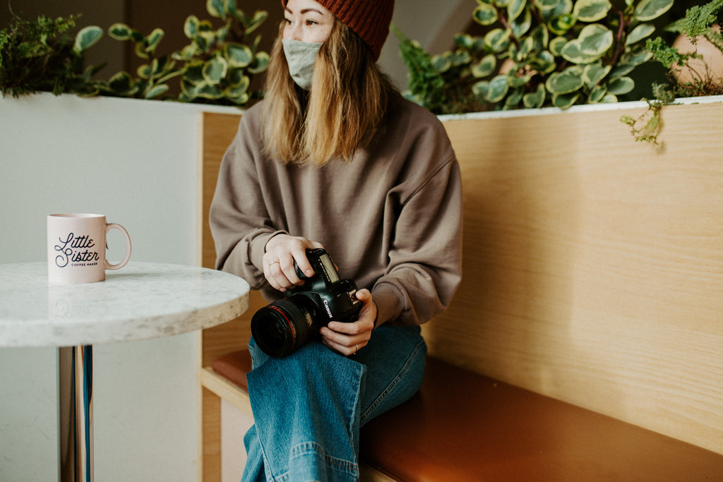 Girl sits on bench with camera in lap, wearing mask and looking away from the camera