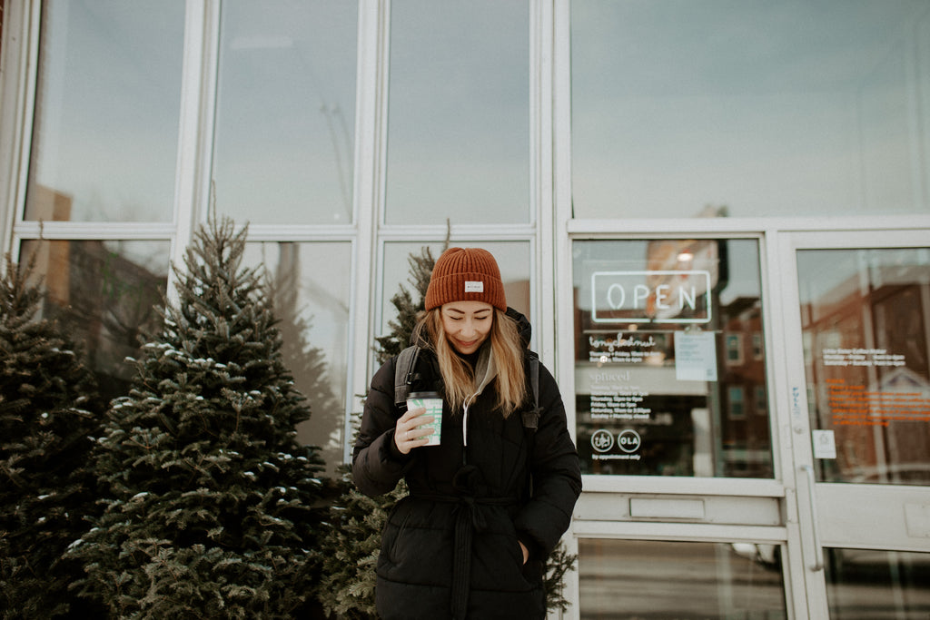 Girl holds coffee cup, smiling, while standing in front of coffeeshop.