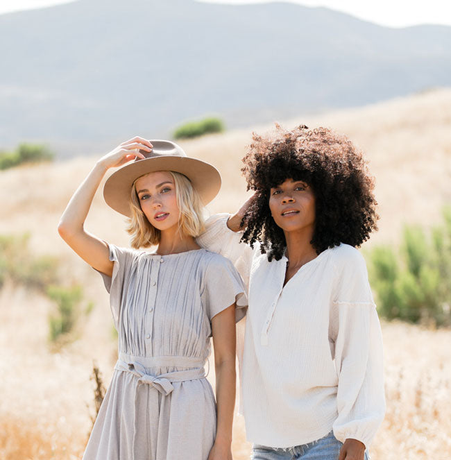 two female friends in trendy clothes looking cool standing in front of golden Californian hills