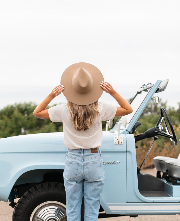 woman standing looking away from the camera, holding the brim of her hat and looking out towards the sea. in the background is a baby blue Ford Bronco.