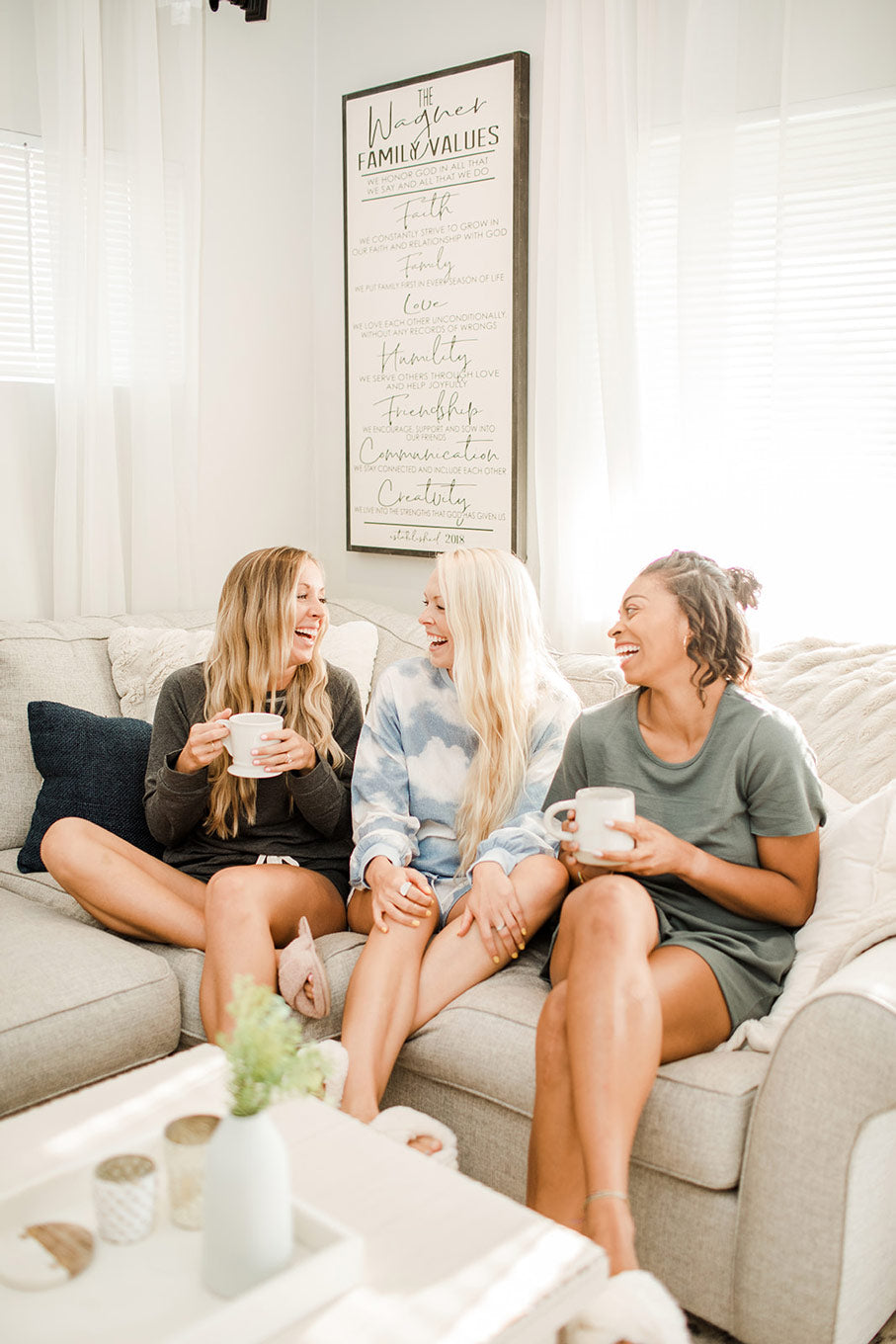 three female friends sitting on a couch and laughing while drinking out of mugs
