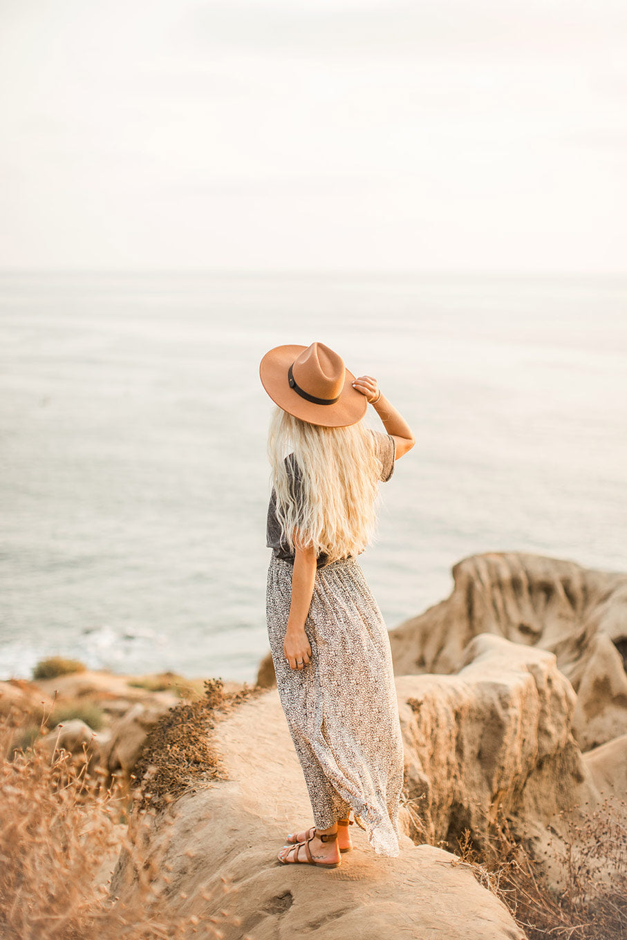 woman with back to camera standing on cliffs overlooking ocean, holding her tan hat