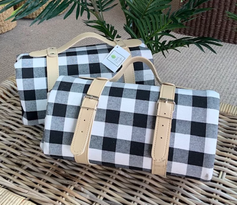 Black and white check cotton picnic rug, with waterproof underside and a cream carry handle.