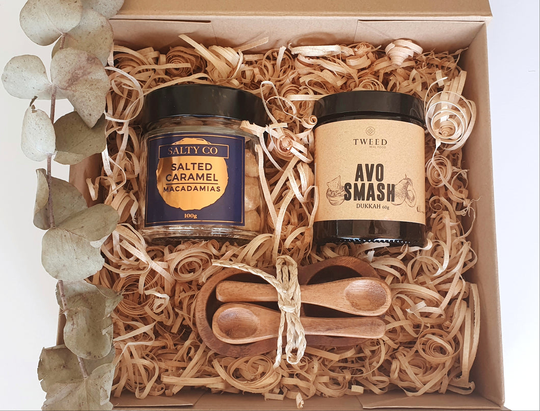 Gift box includes:  Avo Smash Dukkah Salted Caramel Macadamias Acacia wood condiment set