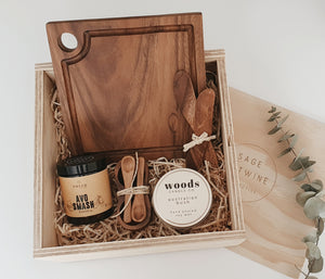 Our beautiful keepsake wooden box includes;  Tweed Real Food Avo Smash Dukkah  Acacia Wood Cheese Board Acacia Wood Spreaders Acacia Wood Condiment Set Woods Candle