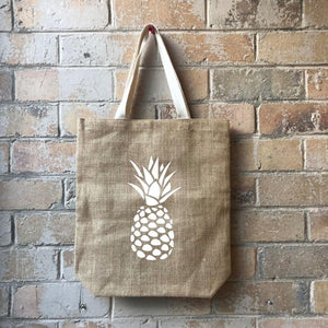 Pineapples never go out of vogue - particularly when printed on your favourite casual shopping bag. Fill to the brim with the freshest of fruit, or your favourite fare - the choice is yours.  Made with non-laminated jute, this bag is designed to be lightweight, fold or roll, so you can take a few where ever you go!  40cm (h) x 36cm (w) White cotton handles 10cm gusset and base