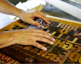 hands moving over wooden and metal letters used in letterpress pritning