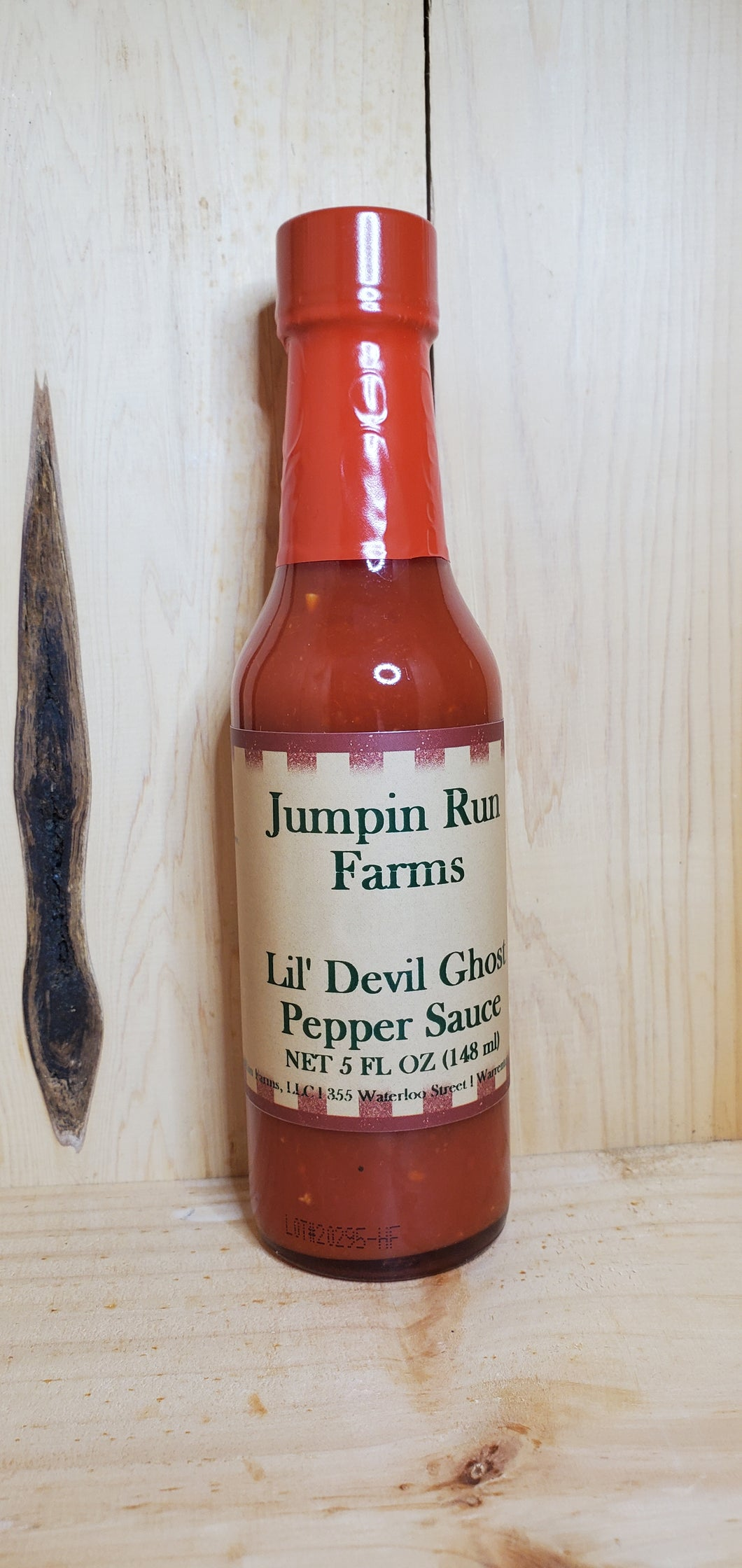 glass bottle of lil devil ghost pepper hot sauce with a red wrapper