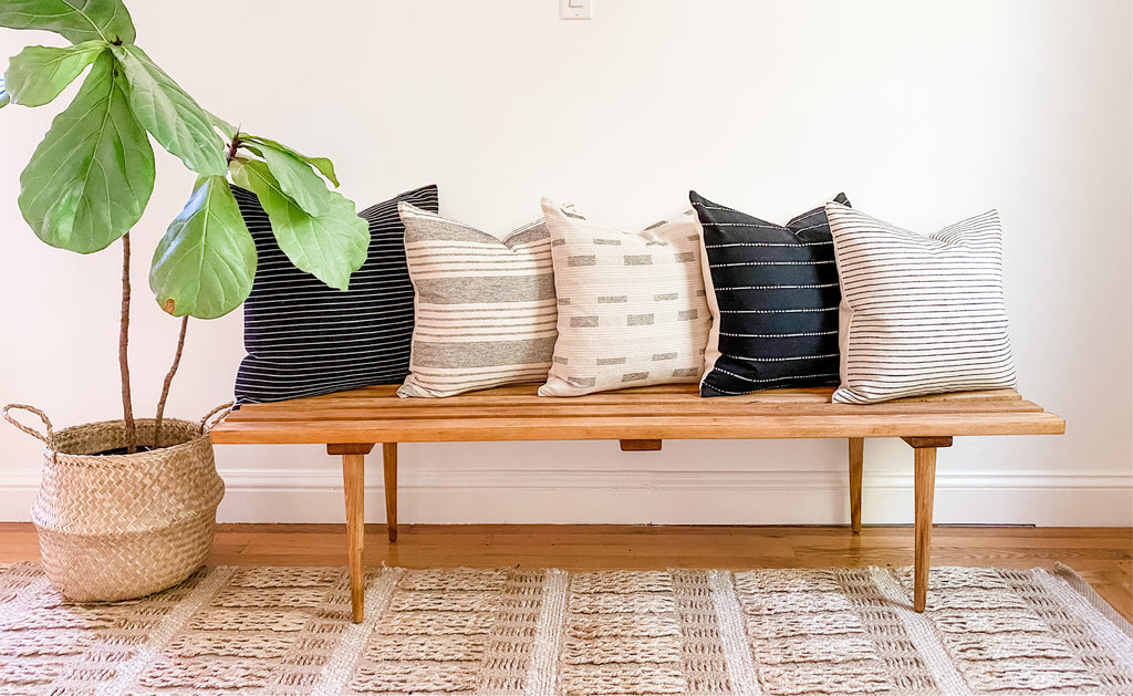 Black and off-white home decor pillow combination on a wood bench