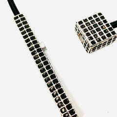 Small silver square with long silver stick on black cord
