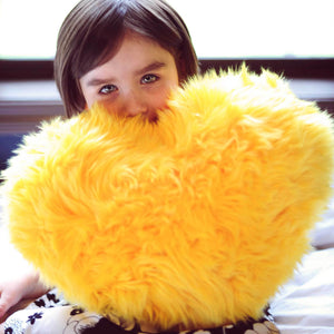 Girl with Yellow faux fur heart shaped pillow.